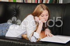 Teenager, Mädchen liest ein Buch auf dem Sofa Stock Photos