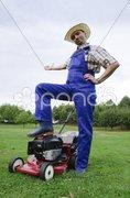 Rasenmäher Mann zeigt auf seinen Rasen Stock Photos