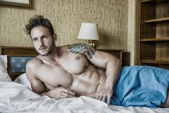 Shirtless sexy male model lying alone on his bed Stock Photos