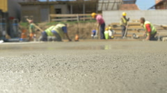 Concrete in focus close up, group of workers in action blurred by Sheyno. Stock Footage