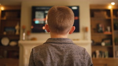 Little boy at home controlling the television, view from behind Stock Footage