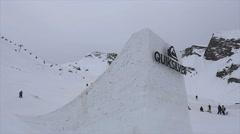 Skier jump from high springboard, make flip, cross ski. Ski resort. Grey weather Stock Footage