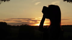 Woman uses a virtual reality glasses in the forest at sunset Stock Footage