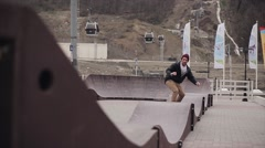Skateboarder ride on springboards on street in city at mountains. Ski lift Stock Footage
