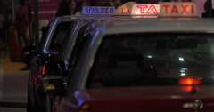On road of night city ride taxi with flaming checker, in the background seen Stock Footage
