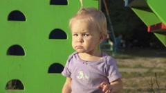 Portrait of frowning little baby girl on the playground, slow motion Stock Footage