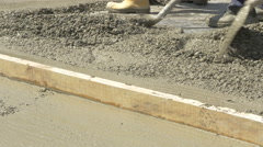 Workers shoveling concrete and leveling floor with plank close up by Sheyno. Stock Footage