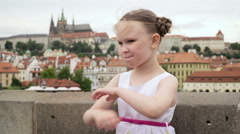 A little girl yawning and laughing with Prague red rooftops in the background. Stock Footage