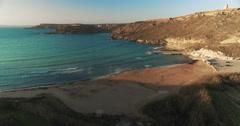 Aerial tilt up from green cliffs to blue Mediterranean  ocean Stock Footage