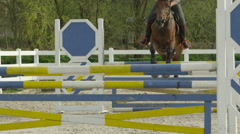 SLOW MOTION: Unrecognizable rider and horse jumping difficult showjumping course Stock Footage