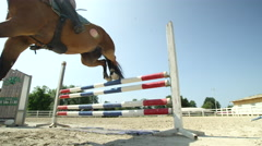 SLOW MOTION: Young competitive rider girl jumping colorful fence on horse show Stock Footage