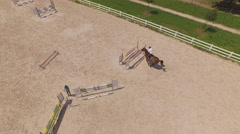 AERIAL: Pro rider jumping a showjumping course with strong brown horse in manege Stock Footage