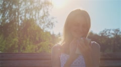 Happy Smiling Girl Using SmartPhone in City Park Sitting on the Bench at sunset Stock Footage