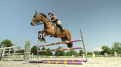 SLOW MOTION: Girl rider having a show jumping lesson with her horse outdoors Stock Footage