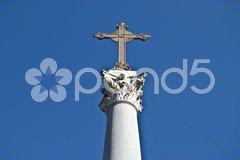Cross on a corinthian pillar against a blue sky Stock Photos