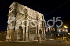 Famous triumphal arch standing next to the colosseum in Rome at night Stock Photos