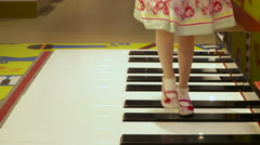 A little girl who is wearing a floral white dress playing a life-size piano Stock Footage
