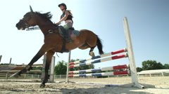 SLOW MOTION: Young competitive rider girl training fence jumping on sandy manege Stock Footage