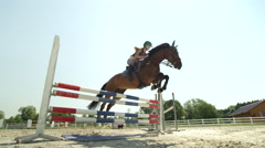 SLOW MOTION: Young rider girl training show jumping with horse in sunny paddock Stock Footage