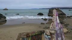 Graffiti Concrete Slabs on desolate beach cloudy day Stock Footage