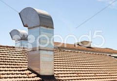 Red tiled roof with chimney on blue sky Stock Photos