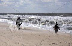 Vermummte Wanderer am stürmischen Strand von Sylt Stock Photos