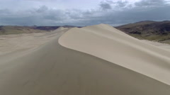 Flying Over Crest of Sand Dune Mountain Stock Footage