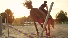 SLOW MOTION: Rider and a horse failing jumping over a fence, knocking poles down Stock Footage