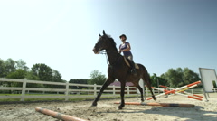 SLOW MOTION: Young girl rider jumping the oxer fence with her horse in paddock Stock Footage