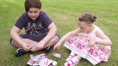 Boy and girl plays card game in social park Stock Footage