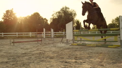 CLOSE UP: Young woman training horse jumping on outdoors arena at sunset Stock Footage