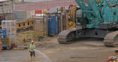 Construction is under way, man watering earth with water from the hose. In the Stock Footage