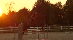 SLOW MOTION: Female rider training showjumping in equestrian center at sunset Stock Footage