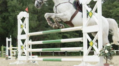 SLOW MOTION: Rider on a white horse competing in equestrian showjumping event Stock Footage