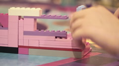Closeup. Little girls hands play with colored lego pieces Stock Footage