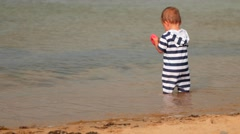 A little boy playing on an ocean beach in the sand Stock Footage