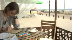 Female artist is drawing picture sitting in cafe outside or terrace Stock Footage
