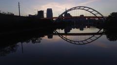 Flying Under Bridge With Nashville Skyline Reflection at Dusk Stock Footage