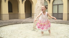 A little girl throws water from a public fountain in the air and laughs Stock Footage