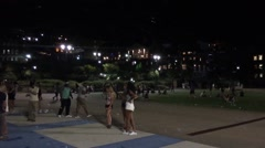 Young group of people hanging around outside in park at night Stock Footage