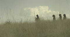 A group of monks in black coats walking through a field of dry grass Stock Footage