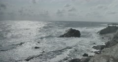 Seascape with rocky shore and rough sea lit by the sun Stock Footage