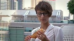 Portrait of a business woman who eats a sandwich in the business district. Stock Footage