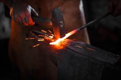 Blacksmith manually forging the molten metal Stock Photos