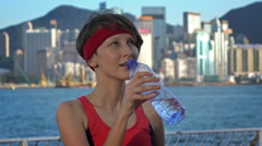 Young woman drinking a water after mornig jogging workout city in background Stock Footage