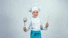 Chef cook child 7-8 years holds soup ladle and whisk standing on white Stock Footage
