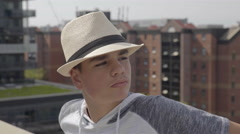 Good looking teenage boy wearing a very fashionable hat out on the terrace. Stock Footage