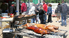 Street food festival spinning lamb baking on a spit people eating meat Stock Footage