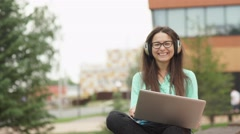 Young beautiful girl sitting with a laptop and headphones. Videochat Stock Footage