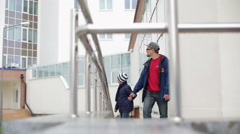Father and son waving and walking up a wheelchair ramp Stock Footage